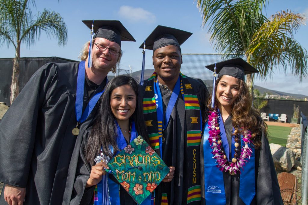 4 graduates in cap in gown from CSUSM looking at the camera