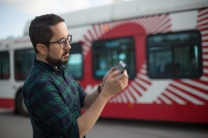 Man in front of MTS bus looking at phone