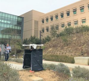 Drone on black stand at UC San DIego in front of large building